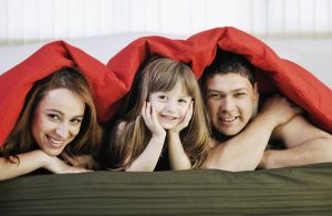 happy family relaxing under the covers