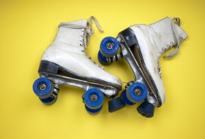 white skates with blue wheels on yellow background