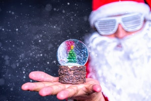 Snowglobe in foreground on hand with party Santa in background