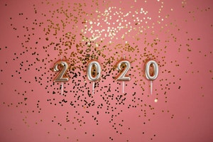 2020 gold candles on pink background with gold confetti