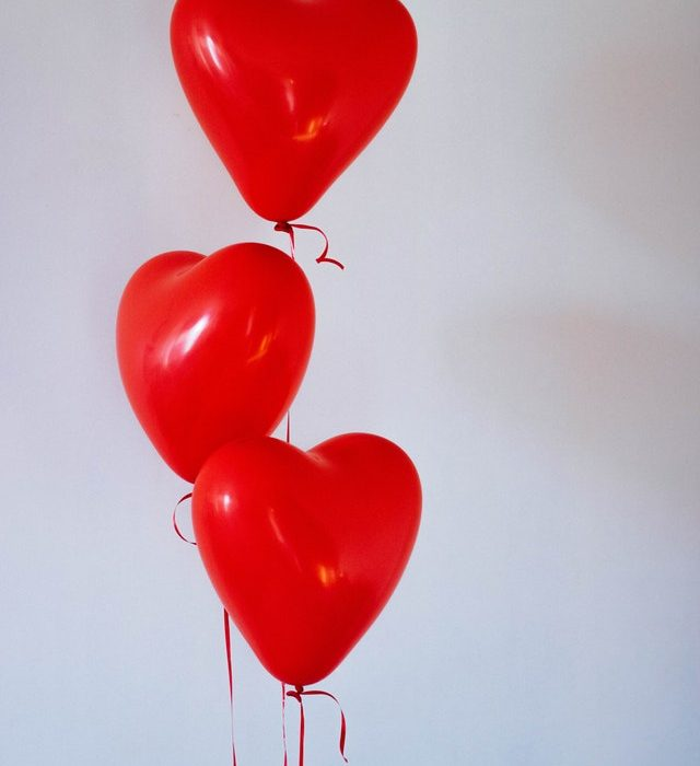 Three red heart-shaped balloons on strings