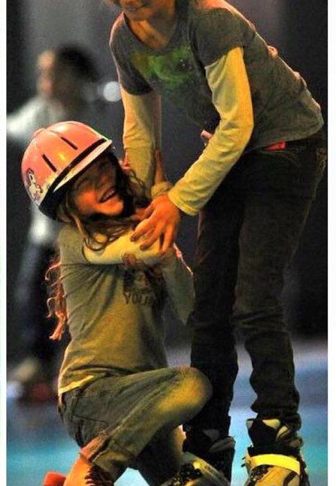 Older girl helping younger girl in helmet learn to skate
