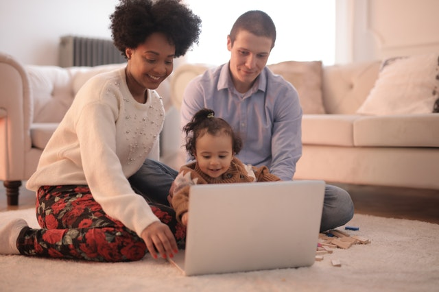 Family sitting on floor with laptop