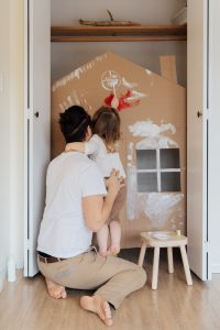 Father and small daughter working on a craft inside