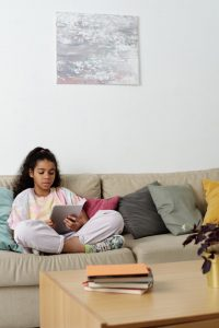 Girl sitting on sofa using tablet