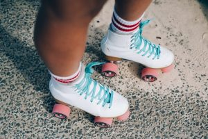 Person wearing white roller skates with pink wheels