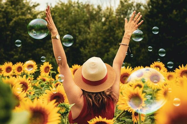 Exuberant woman in straw hat surrounded by yellow sunflowers and bubbles