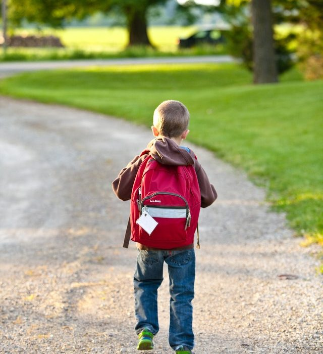 Small boy with red backpack walking down driveway for school