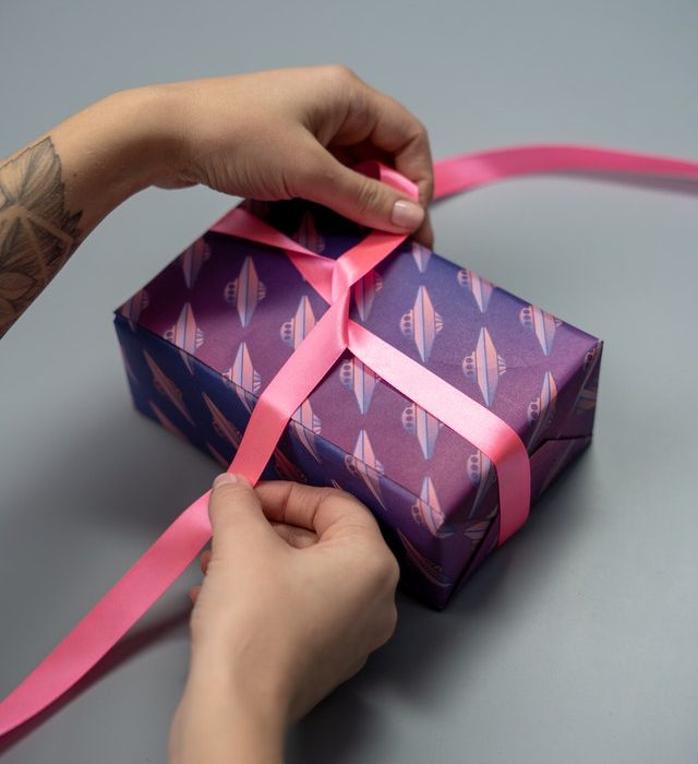 Hands tying bow on wrapped gift