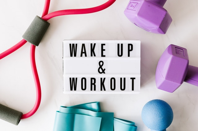 Wake up and work out sign on white background with gym equipment