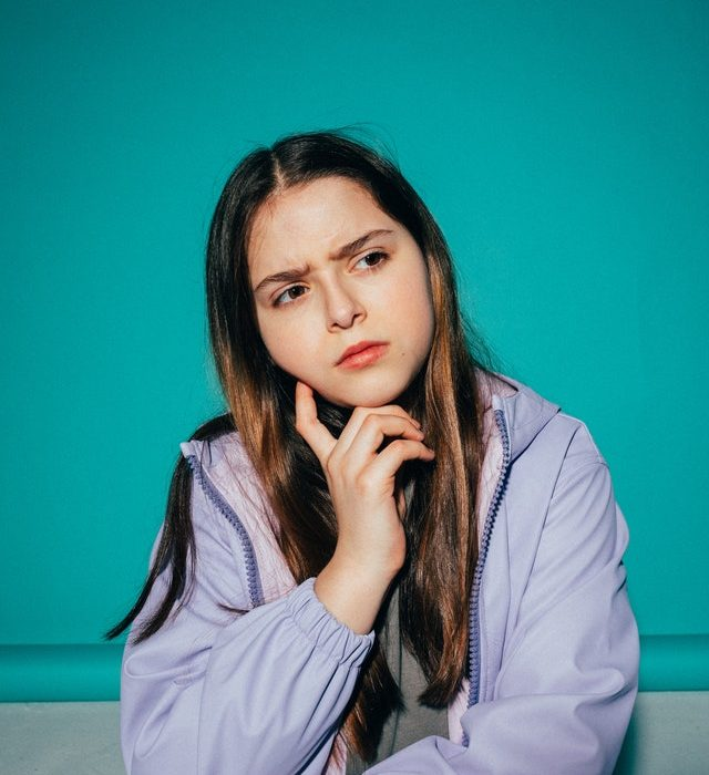 Girl in purple jacket touching chin and thinking with furrowed brow